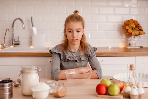 Adolescente blonde dans une robe grise va faire cuire la tarte aux pommes traditionnelle dans la nouvelle cuisine