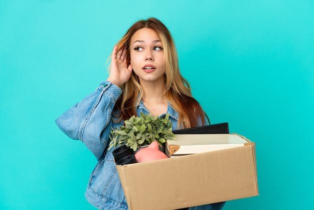 Adolescente blonde faisant un geste tout en ramassant une boîte pleine de choses en écoutant quelque chose en mettant la main sur l'oreille