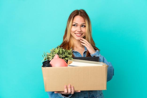Adolescente blonde faisant un geste tout en ramassant une boîte pleine de choses regardant sur le côté et souriant
