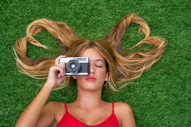 Adolescente blonde avec des formes de coeur de cheveux se trouvant