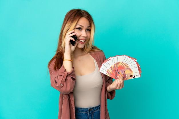 Adolescente blonde prenant beaucoup d'euros sur fond bleu isolé en gardant une conversation avec le téléphone mobile
