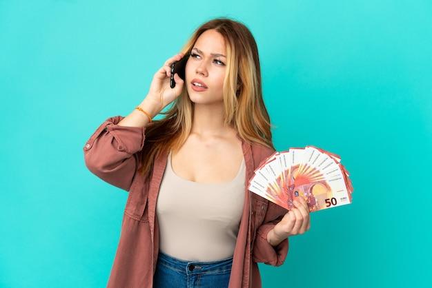 Adolescente blonde prenant beaucoup d'euros sur fond bleu isolé tenant du café à emporter et un mobile