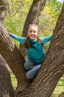 Une adolescente blonde riante a grimpé sur un arbre étalé dans le parc