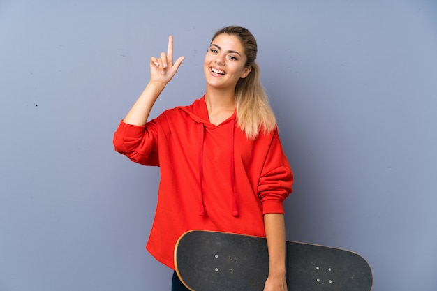 Une adolescente blonde skater sur un mur gris dans le but de réaliser la solution tout en levant un doigt