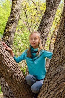 Une adolescente blonde souriante a grimpé sur un arbre étalé dans le parc