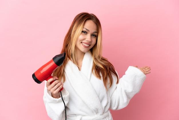 Adolescente blonde tenant un sèche-cheveux sur fond rose isolé tendant les mains sur le côté pour inviter à venir