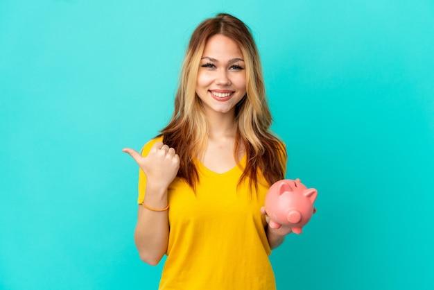 Adolescente blonde tenant une tirelire sur fond bleu isolé pointant vers le côté pour présenter un produit
