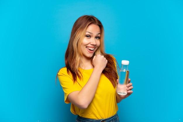 Adolescente avec une bouteille d'eau sur fond bleu isolé célébrant une victoire