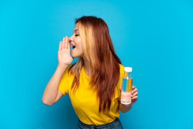 Adolescente avec une bouteille d'eau sur fond bleu isolé criant avec la bouche grande ouverte sur le côté