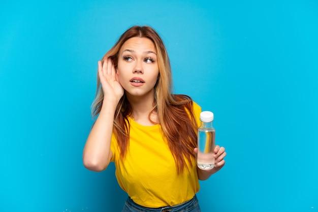 Adolescente avec une bouteille d'eau sur fond bleu isolé écoutant quelque chose en mettant la main sur l'oreille