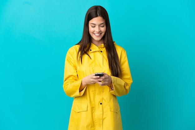 Adolescente brésilienne portant un manteau imperméable sur fond bleu isolé envoyant un message avec le mobile