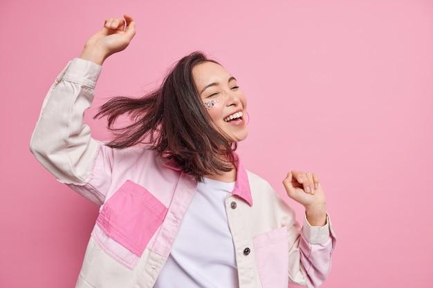 Une adolescente brune joyeuse et optimiste pleine d'énergie serre la main danse carefre pose à moitié tournée contre le mur rose célèbre la victoire exprime des émotions positives habillées avec désinvolture.