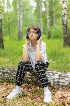 Une adolescente avec un casque écoute de la musique dans un parc de la ville, des loisirs de plein air pour les jeunes
