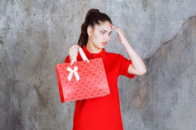 Adolescente en chemise rouge tenant un sac à provisions rouge et a l'air confus et réfléchi