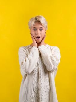 Adolescente choquée avec une courte coupe de cheveux blanche portant un pull en tricot blanc