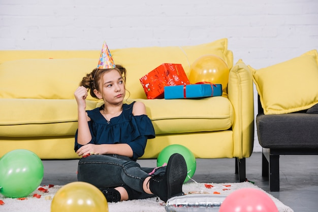 Une adolescente en colère assise sur le tapis blanc avec des ballons à la maison