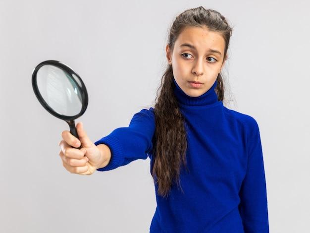 Adolescente concentrée qui s'étend en regardant la loupe à travers elle isolée sur un mur blanc