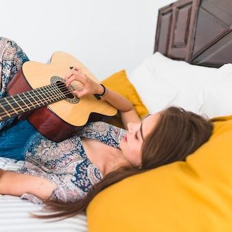Adolescente, coucher, jouer, guitare