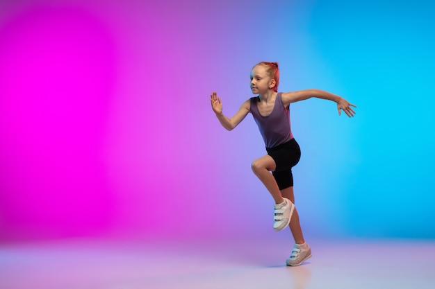 Adolescente courir, faire du jogging sur fond de studio néon rose-bleu dégradé en mouvement