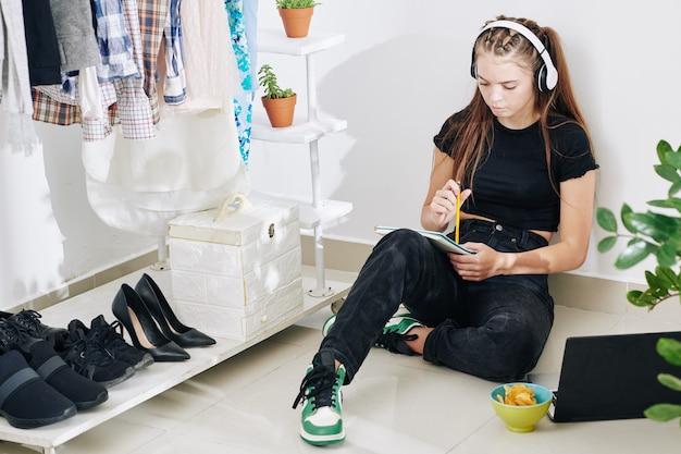 Adolescente créative dans les écouteurs assis sur le sol dans son fermé, manger des croustilles, écouter de la musique et écrire de la poésie