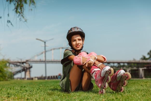 Adolescente dans un casque apprend à monter sur des patins à roulettes à l'extérieur