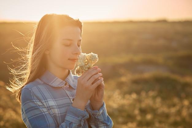 Une adolescente dans un champ au coucher du soleil avec des fleurs dans ses mains.
