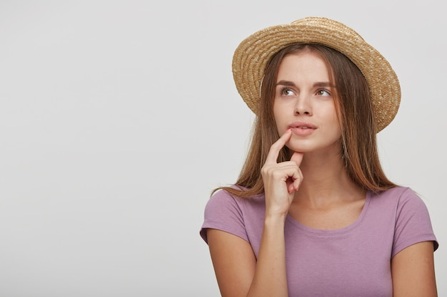 Adolescente dans un chapeau de paille avec un ruban rose regarde de côté perplexe, essayant de se souvenir de quelque chose d'important