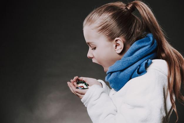 Adolescente dans une écharpe tricotée mange des médicaments des paumes.