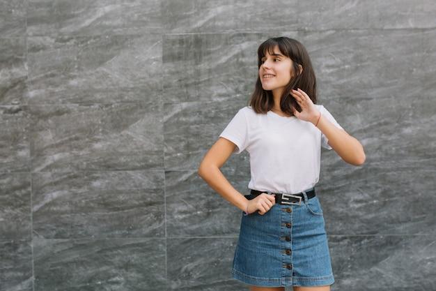 Adolescente dans des verres et des bretelles posant près du mur gris.