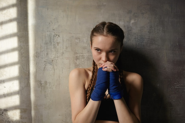 Adolescente déterminée sérieuse avec deux tresses posant au mur texturé blanc, portant des bandages bleus, serrant les mains sur son visage, prêt pour la classe de boxe