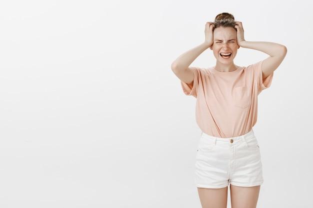 Adolescente en détresse et inquiète posant contre le mur blanc