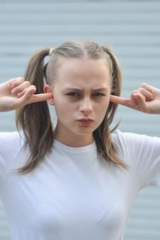 Adolescente avec les doigts dans les oreilles