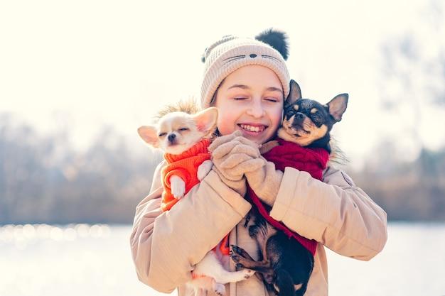 Une adolescente embrasse ses deux chiens chihuahua chiot et chien adulte. chiot chihuahua