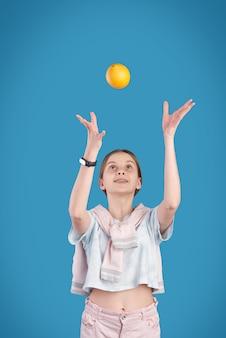 Adolescente énergique jetant de l'orange fraîche tout en jouant avec elle devant la caméra sur fond bleu dans l'isolement