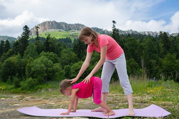 Une adolescente enseigne à un petit enfant à faire des exercices de yoga dans la nature sur fond de montagnes