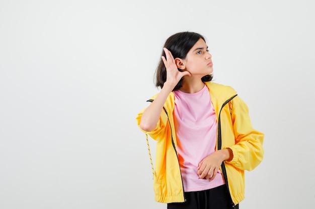 Une adolescente entendant une conversation privée en t-shirt, une veste et l'air concentré. vue de face.