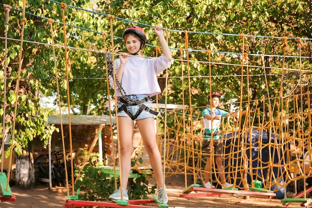 Adolescente, escalade dans le parc aventure