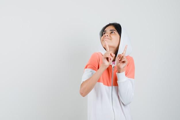 Adolescente essayant d'attraper le rythme de la musique en veste blanche et à la recherche amusée.