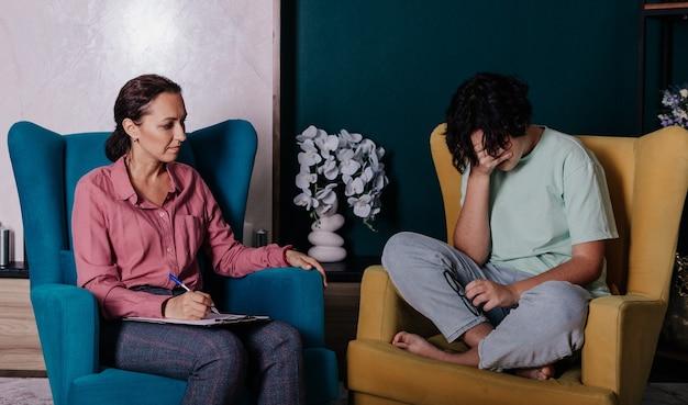 Une adolescente est assise sur une chaise lors d'une réception avec une psychologue