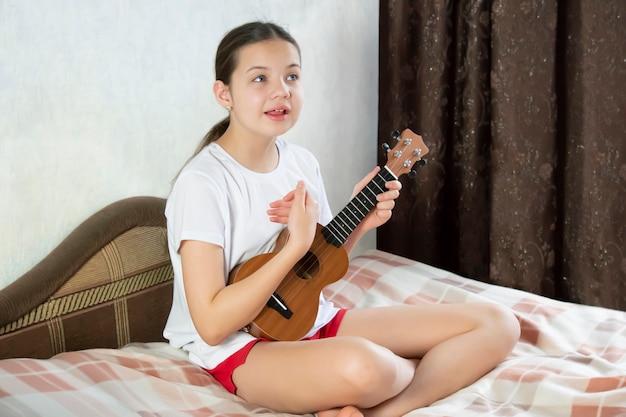 Une adolescente est assise sur le lit, joue du ukulélé et chante