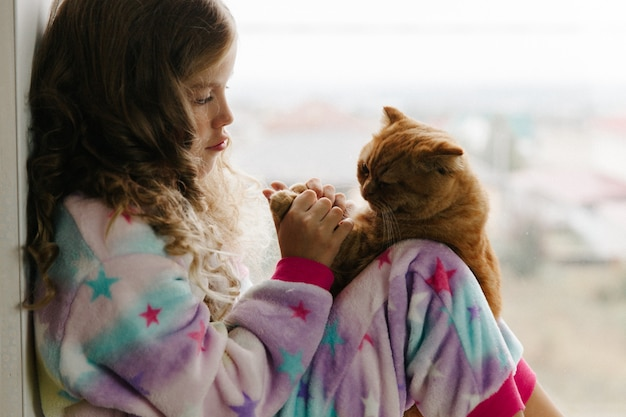 Une adolescente est assise en pyjama à la fenêtre de la maison et tient un chat roux. rester à la maison.