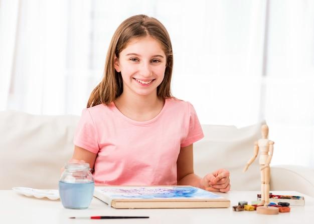 Une adolescente est heureuse de son travail de peinture