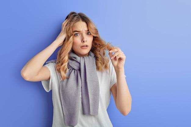 Une adolescente est stressée debout avec la main sur la tête