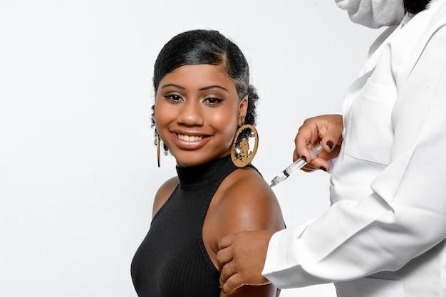 Une adolescente est vaccinée par un professionnel de la santé