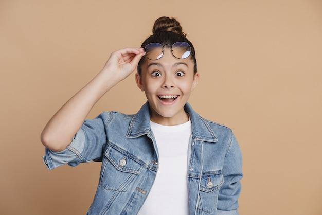 Une adolescente étonnée et mignonne leva ses lunettes de ses yeux. petite fille surprise sur fond marron