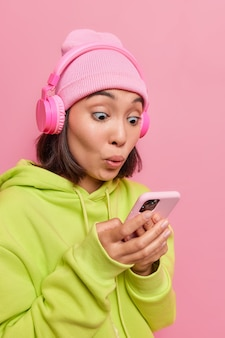 Une adolescente étonnée regarde surprise par le smartphone stressé par la lecture de mauvaises nouvelles reçoit un reçu de facture porte un chapeau et un sweat-shirt pose contre le mur rose