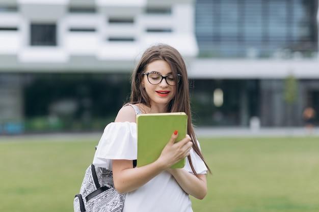 Adolescente étudiante à l'aide d'un ordinateur tablette blanc.