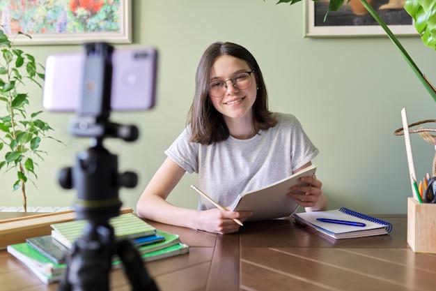 Une adolescente étudiante étudie en ligne à l'aide d'un smartphone, d'une vidéoconférence, d'un appel vidéo, d'un enseignement à distance, d'un apprentissage à la maison