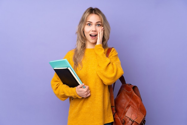 Adolescente étudiante sur mur violet avec surprise et expression faciale choquée