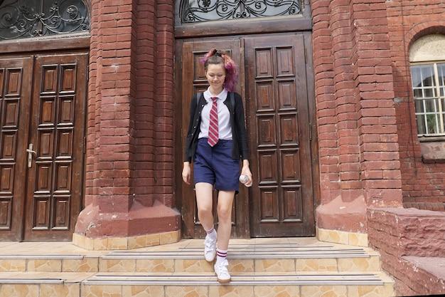 Adolescente étudiante en uniforme avec sac à dos, fond d'école de construction. retour à l'école, retour au collège, éducation, concept ados